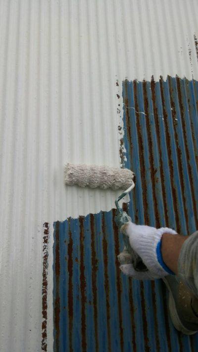 藤沢市メゾンタイプで追加工事のトタン屋根をローラーで塗り替えている写真