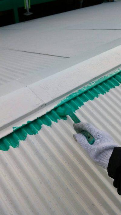藤沢市メゾンタイプで追加工事のトタン屋根をハケで塗っている写真