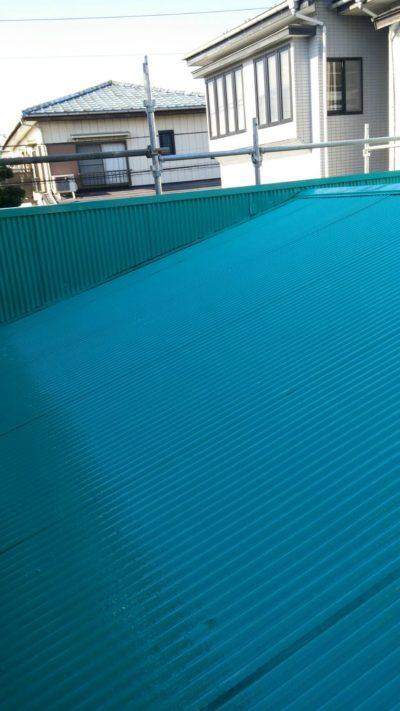 藤沢市メゾンタイプ追加工事でトタン屋根の中塗りと上塗りをしている写真