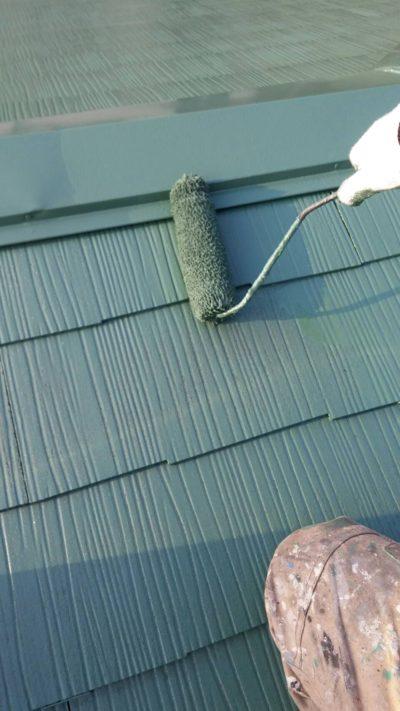 屋根をローラーで塗っている写真
